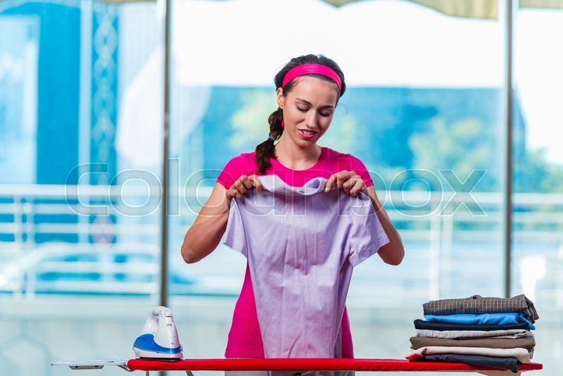Stock image of 'Young woman ironing clothing on board'