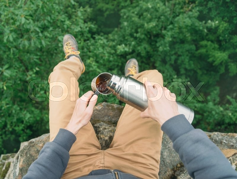Stock image of 'Traveler young man sitting on top of rock over the summer forest and pouring tea from thermos to cup. Point of view shot'