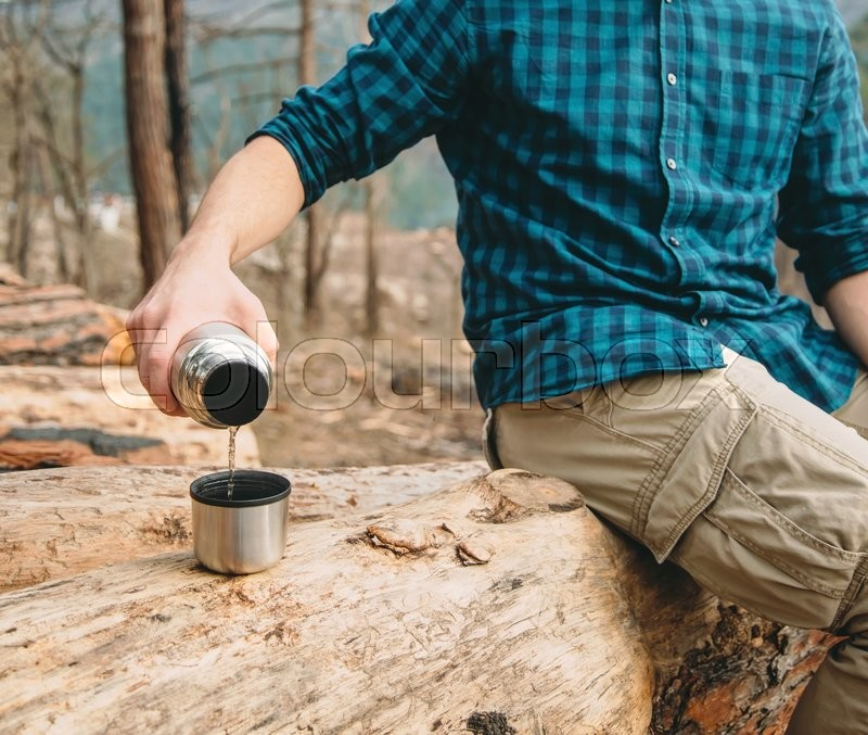 Stock image of 'Unrecognizable hiker young man pouring tea from thermos to cup in the forest outdoor'