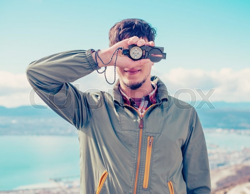 Stock image of 'Smiling traveler young man covered his face with compass on background of sea outdoor'