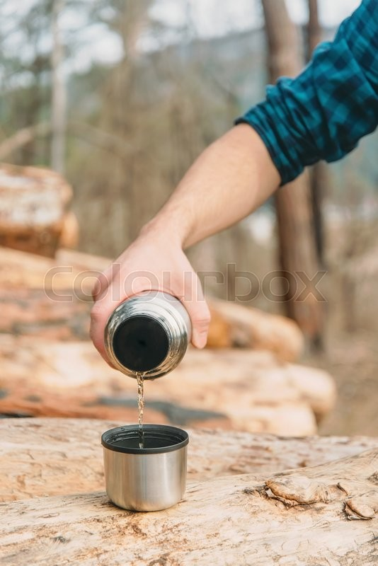 Stock image of 'Unrecognizable young man pouring tea from thermos to cup in the forest outdoor, close-up view of hand'