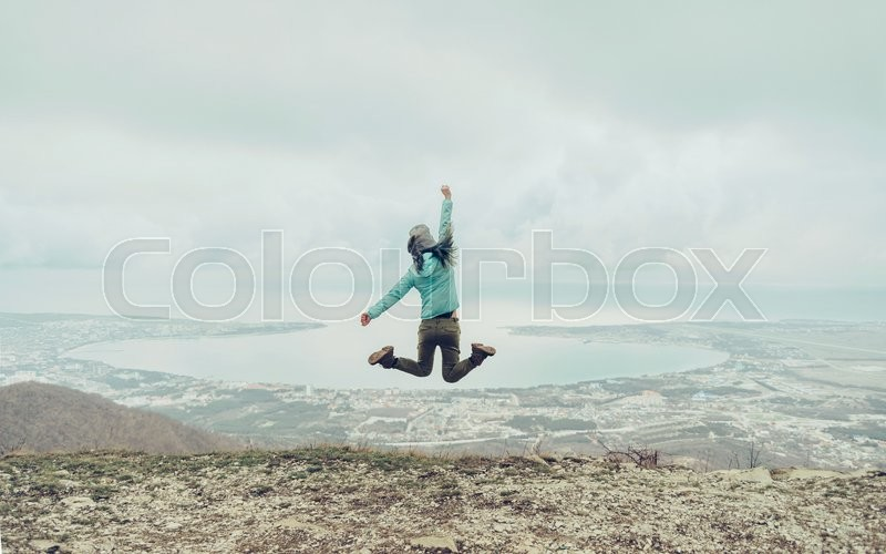 Stock image of 'Happy traveler young woman jumping on mountain on background of sea bay, rear view'