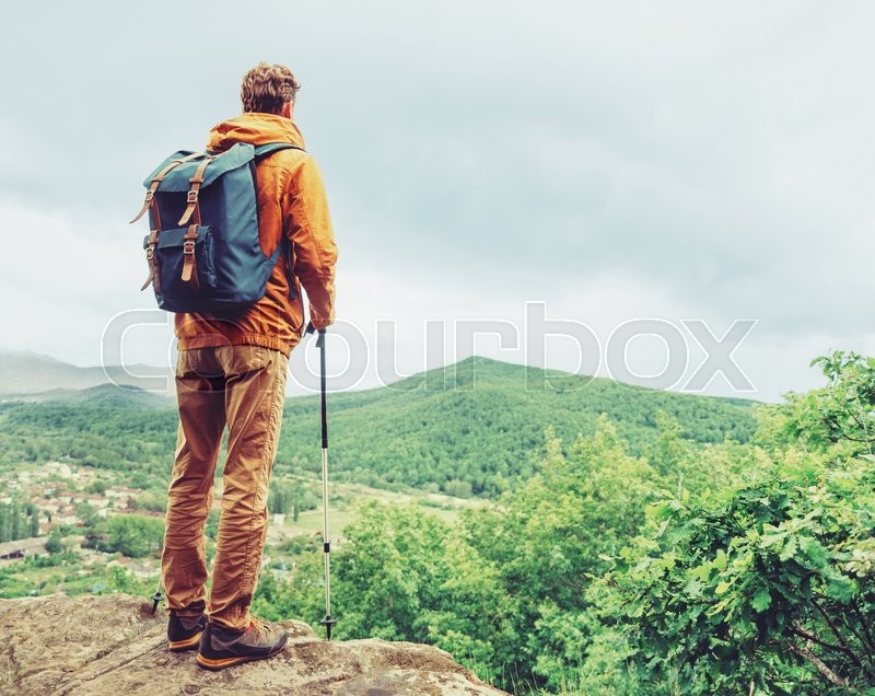 Stock image of 'Hiker young man with backpack and trekking poles standing on edge of cliff and looking at the mountains in summer outdoor, rear view'