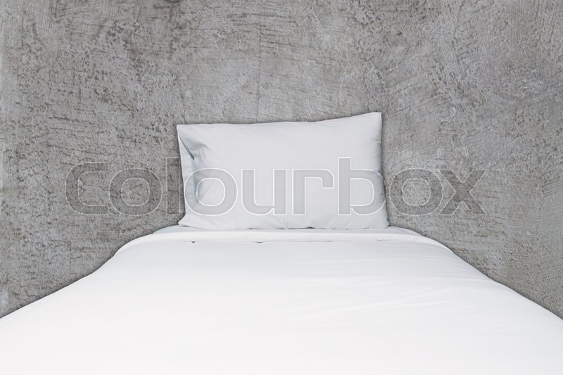 Close up white bedding and pillow on abstract gray concrete texture background, stock photo