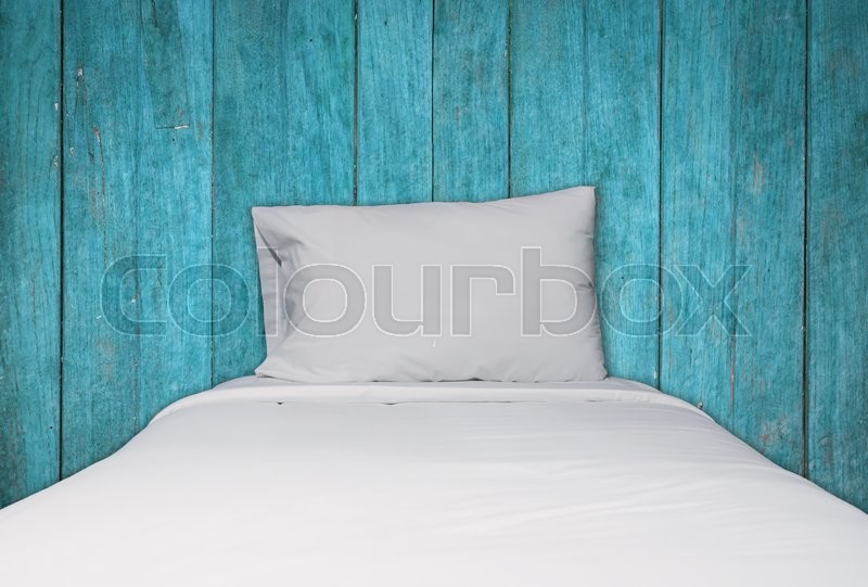 Stock image of 'Close up white bedding and pillow on blue wooden texture background, stock photo'
