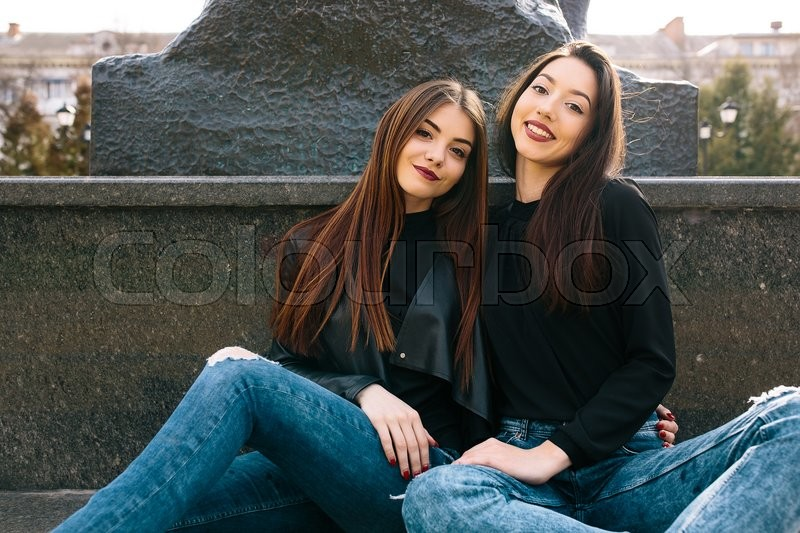 Stock image of 'Two young adult women sitting in a park and posing for the camera'