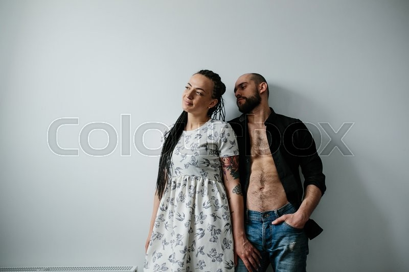Stock image of 'man and woman posing against a white wall'