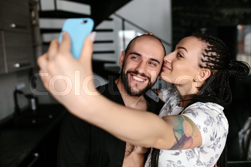 Stock image of 'handsome man and beautiful woman making selfie indoors'