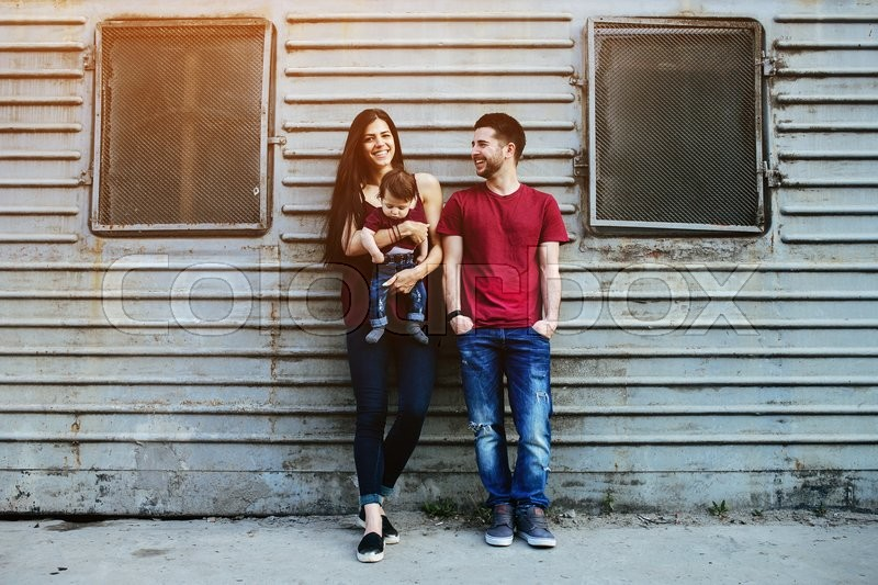 Stock image of 'young beautiful family with child posing on the building background'
