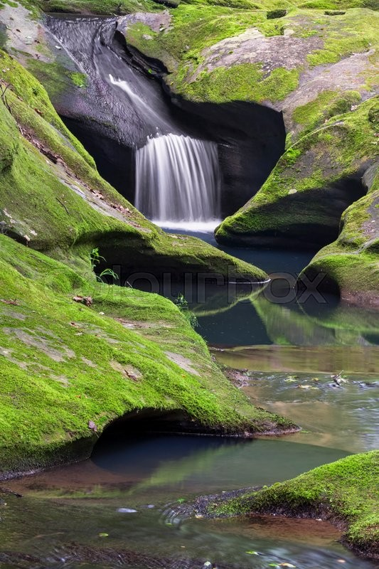 Stock image of 'A small waterfall flows through sculpted, mossy sandstone above the main plunge of Robinson Falls at Boch Hollow Nature Preserve in Ohio's Hocking Hills.'