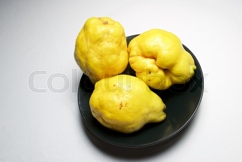 Stock image of 'Quince pieces in a black bowl.'