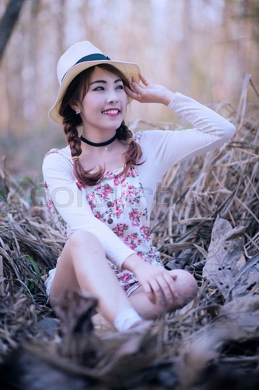Stock image of 'Outdoor portrait girl in the meadow, teenage asian girl wearing a hat.'