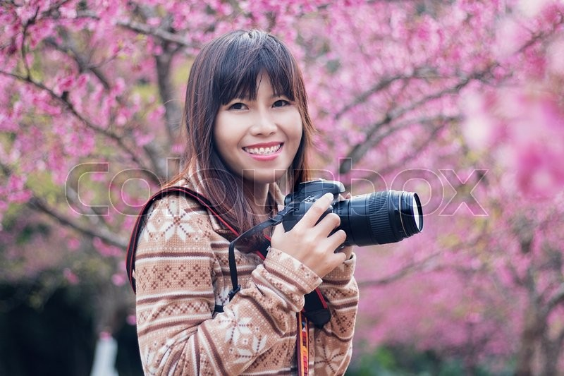 Stock image of 'Women photographer smilling and take a picture in flowers gardening and blurred background'