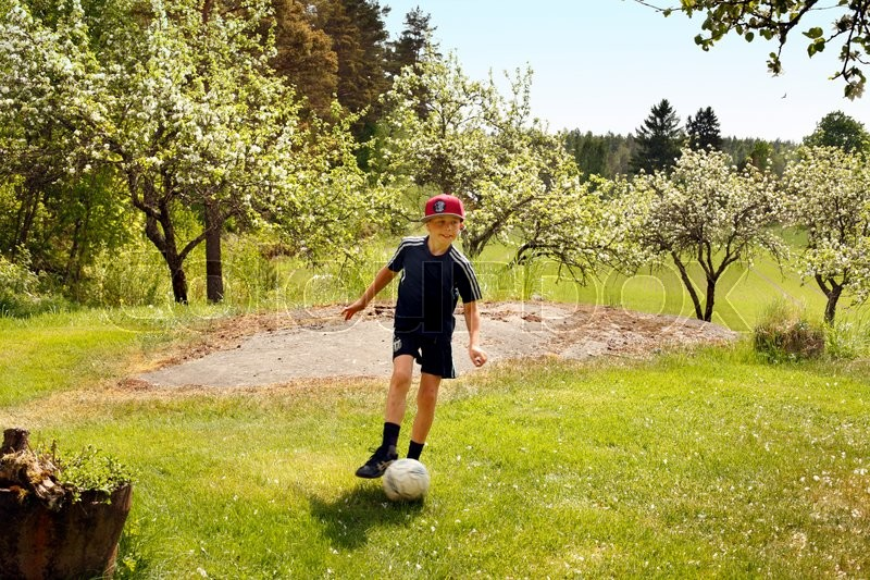 Stock image of 'young schoolboy enjoying himself playing football in the countryside on lawn in front of blooming apple trees'