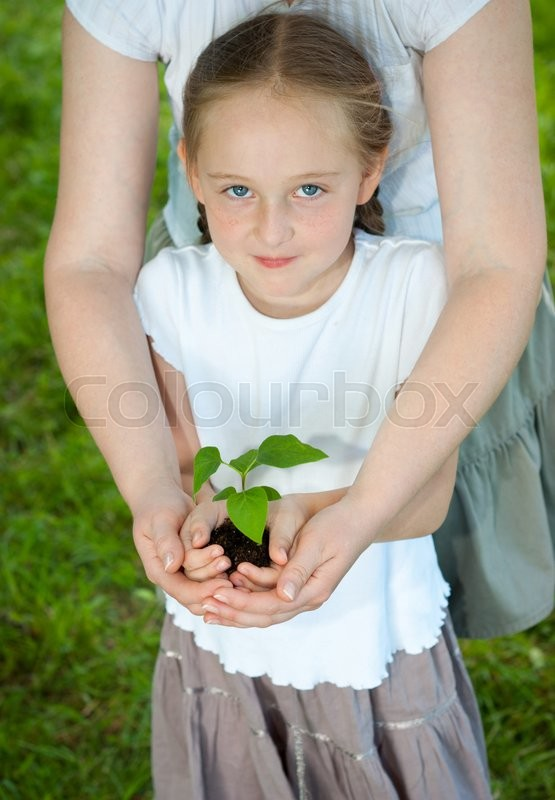 Stock image of 'Girl with her mother holding a young plant in hands. Ecology concept'