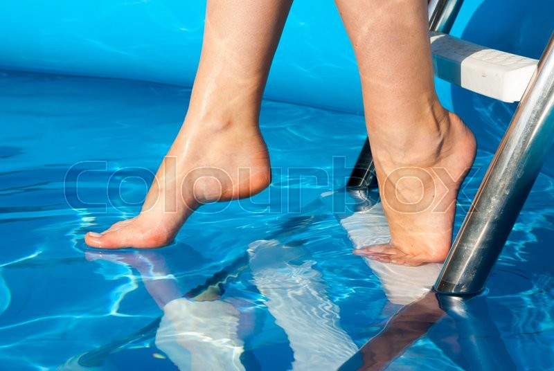 Stock image of 'Human legs on the blue water'