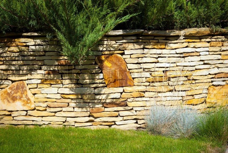 Stock image of 'A stone wall in garden with bushes grass'