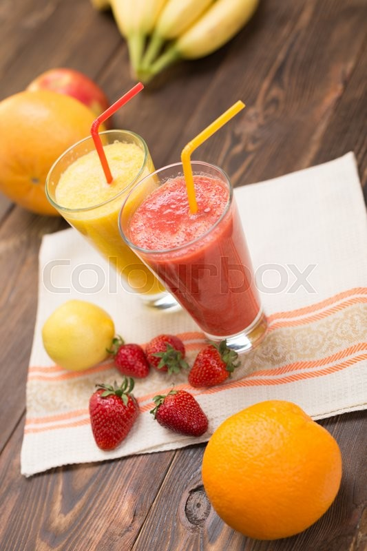 Stock image of 'Fresh fruit smoothies on kitchen table in a two glass'