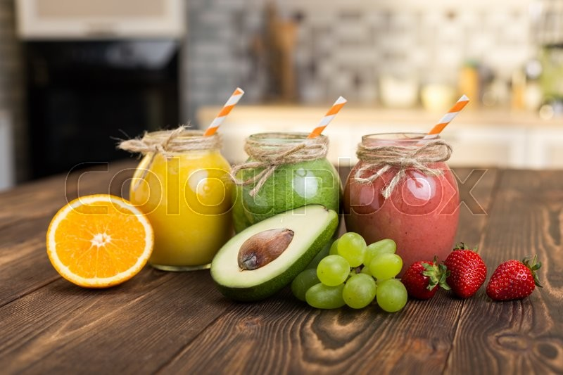 Stock image of 'Fresh fruit and jar with smoothie on kitchen table'