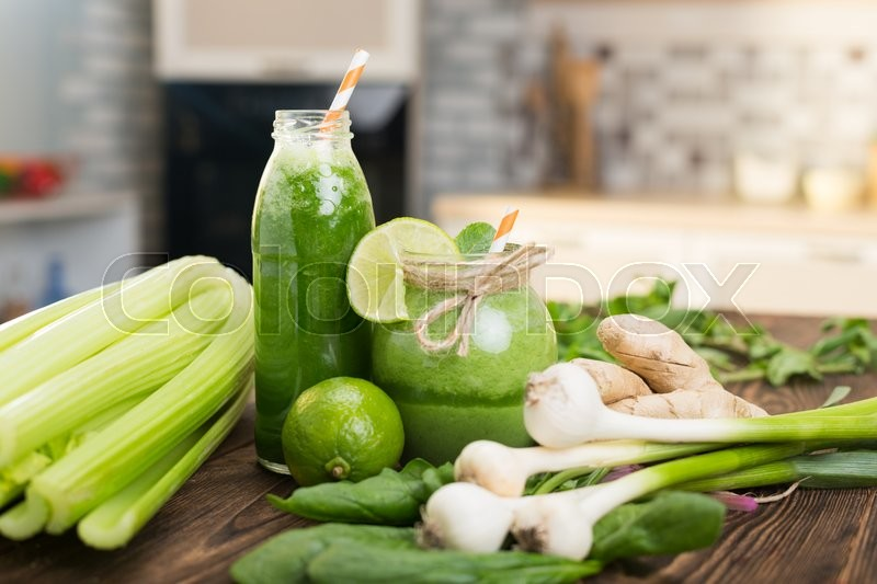 Stock image of 'Fresh fruits and bottle with green smoothies on kitchen table'
