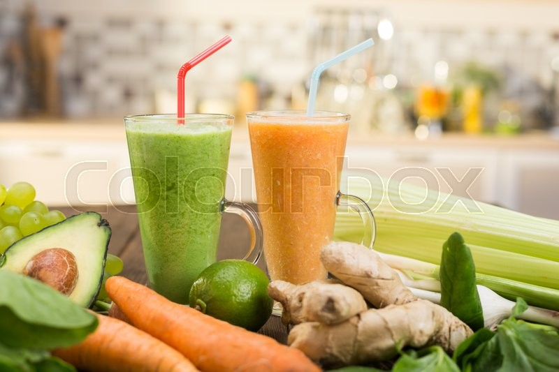 Stock image of 'Fresh vegetable smoothies on wooden kitchen table'