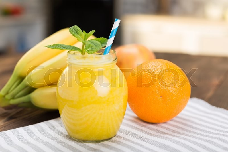 Stock image of 'Fresh fruit smoothies on kitchen table in a small jar'