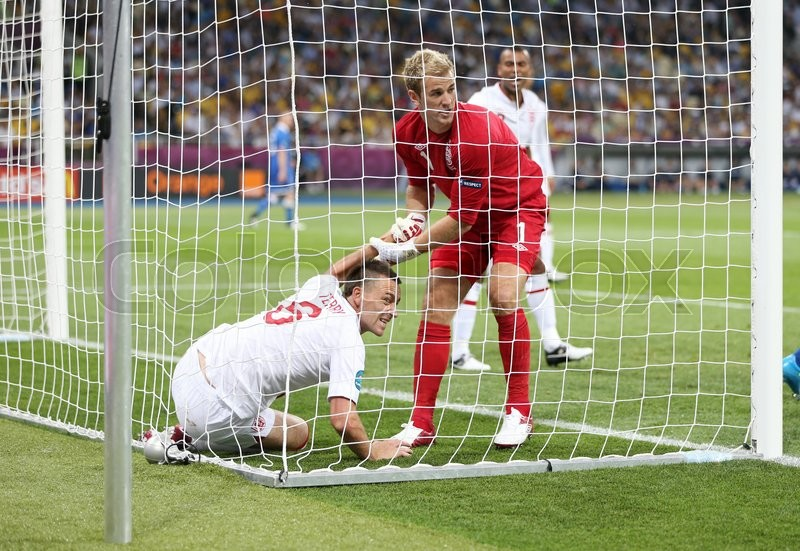 Editorial image of 'KYIV, UKRAINE - JUNE 24, 2012: Goalkeeper Joe Hart of England helps John Terry to get up during UEFA EURO 2012 Quarter-final game against Italy at Olympic stadium in Kyiv, Ukraine'