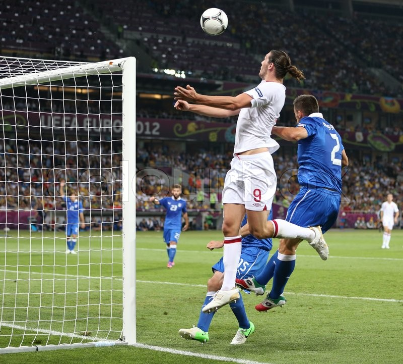 Editorial image of 'KYIV, UKRAINE - JUNE 24, 2012: Andy Carroll of England (in White) fights for a ball with Italian defenders during their UEFA EURO 2012 Quarter-final game at Olympic stadium in Kyiv, Ukraine'