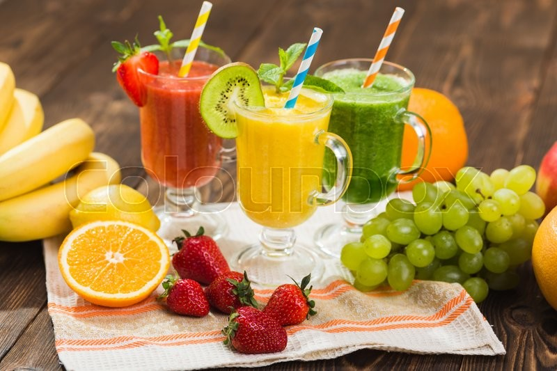 Stock image of 'Fresh fruit and vegetable smoothie on kitchen table in glass'