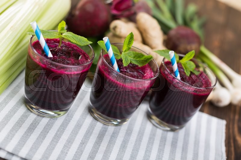 Stock image of 'Smoothie of beets and fresh vegetables on kitchen table'