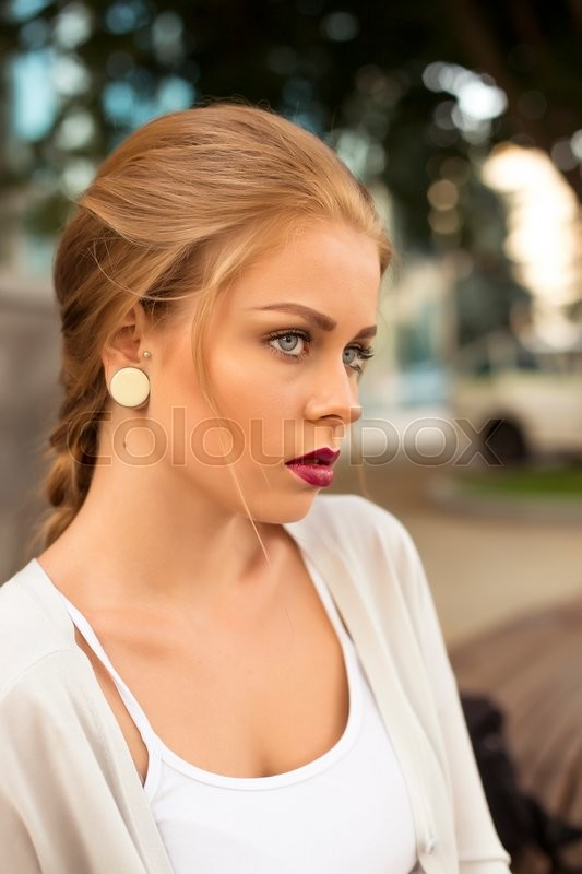 Stock image of 'Young smiling woman outdoors portrait. Soft sunny colors.Close portrait.'