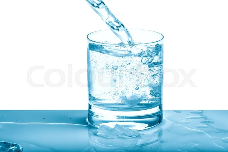Stock image of 'Sparkling water pouring into glass over bright background. Cold drink. Blue colored picture'