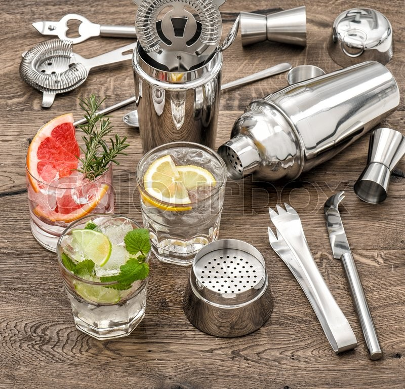 Stock image of 'Drinks with ice and tonic water. Cocktail making bar accessories, shaker, glasses, mint leaves'