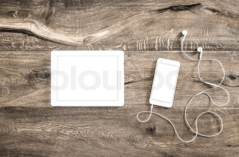 Stock image of 'Digital devices on wooden background. Smart phone with headphones and tablet pc on office desk'