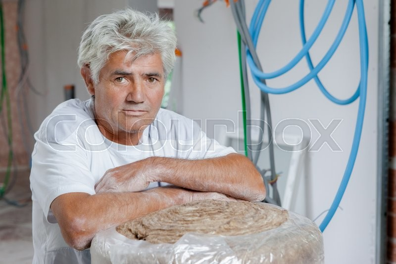 Stock image of 'Builder stood with loft insultaion'