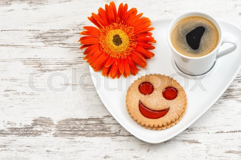 Stock image of 'Cup of black coffee with smiled cookie on wooden background. Funny breakfast'