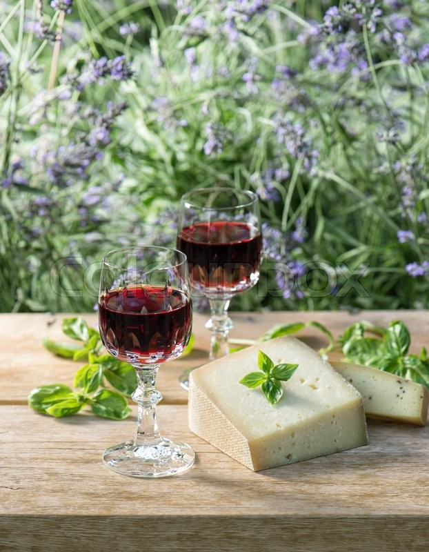 Stock image of 'Cheese with red wine on wooden table outdoors. Food still life'