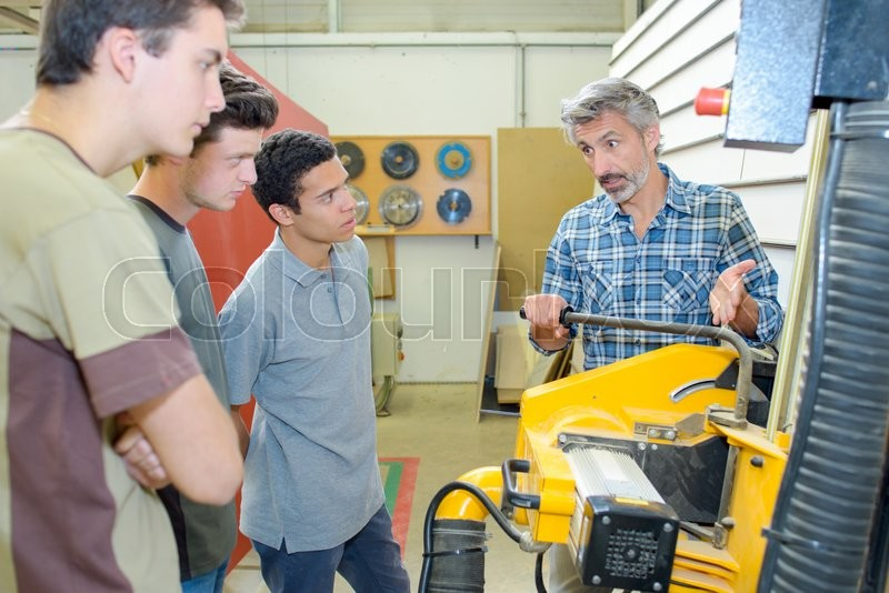 Stock image of 'Teacher showing machinery'