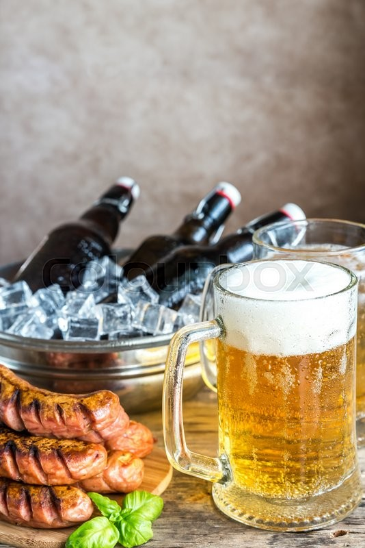Stock image of 'Grilled sausages and mugs of beer'