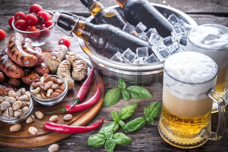 Stock image of 'Grilled sausages with appetizers and mugs of beer'