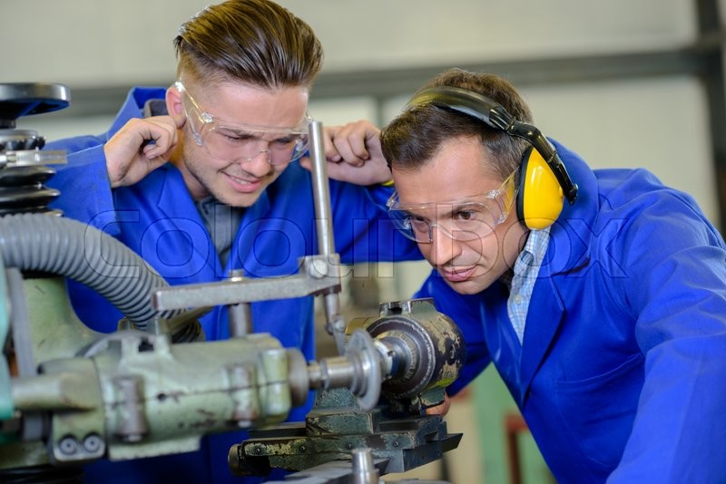 Stock image of 'Engineer using machine apprentice with fingers in ears'