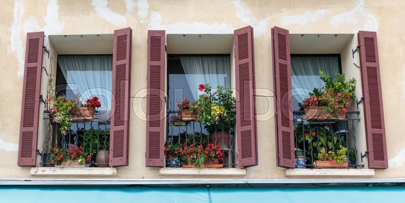 Stock image of 'Windows in an old house decorated with flowers'