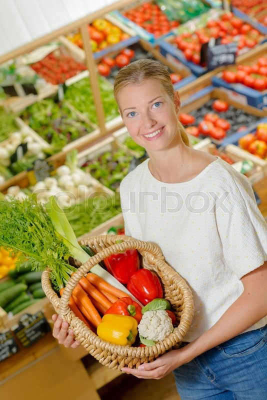 Stock image of 'Woman by a vegetable stand'