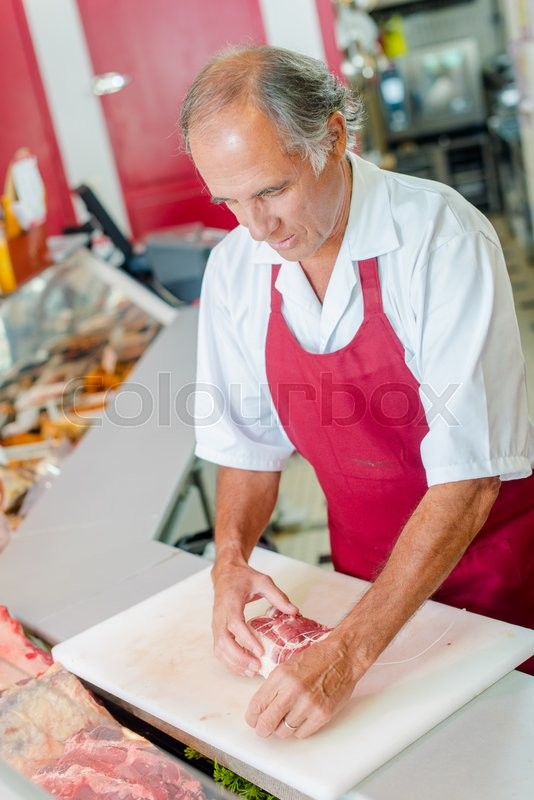 Stock image of 'Preparing meat for a customer'