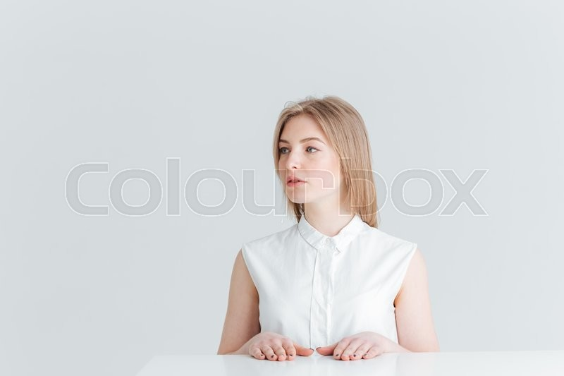 Stock image of 'Beautiful blonde woman sitting at the table and looking away isolated on a white background'