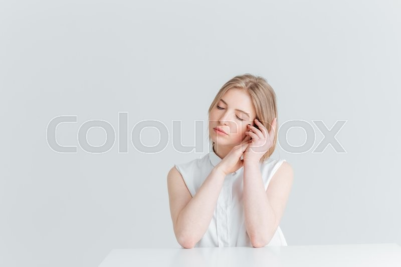 Stock image of 'Beauty portrait of a young relaxed woman sitting at the table isolated on a white background'