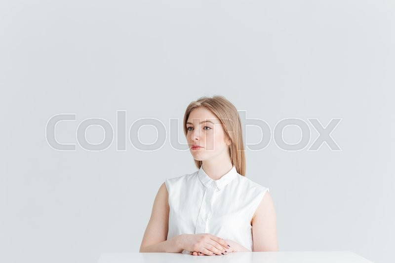 Stock image of 'Attractive blonde woman sitting at the table isolated on a white background and looking away'