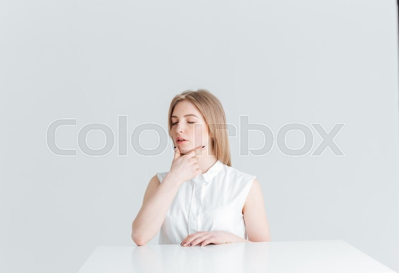 Stock image of 'Beauty portrait of a young woman with closed eyes sitting at the table isolated on a white background'