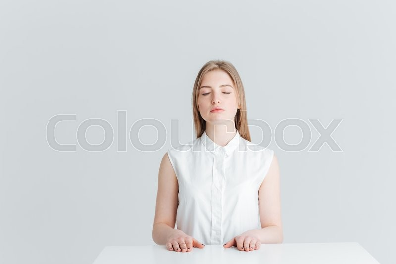 Stock image of 'Beauty portrait of relaxed woman with closed eyes sitting at the table isolated on a white background'