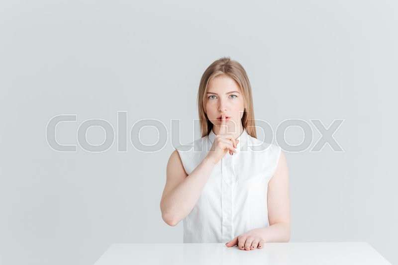 Stock image of 'Young woman sitting at the table and showing finger over lips isolated on a white background'